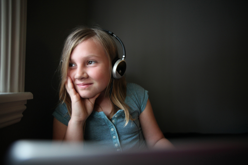 A teenage girl wearing headsets having fun on the computer.
