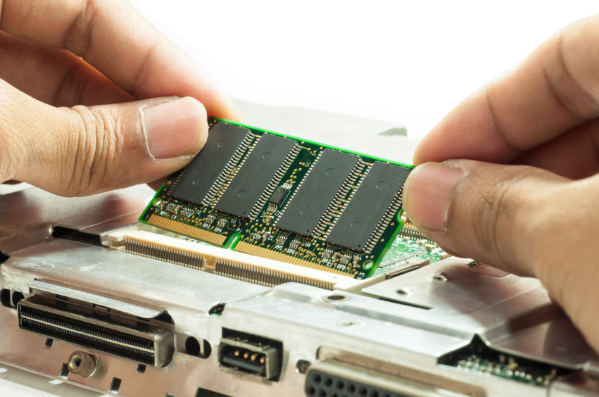 Human hand placing the RAM memory card on laptop computer motherboard