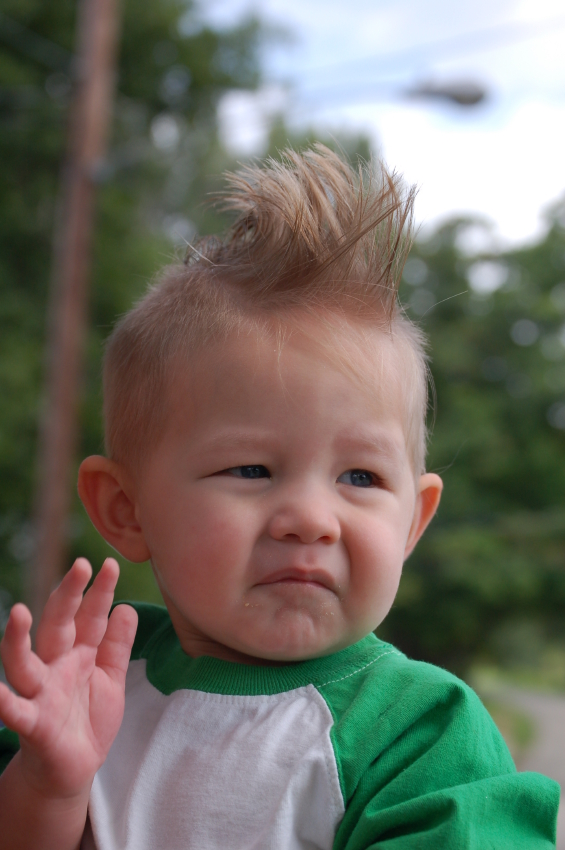 A baby with spiky hair and sad expression waves goodbye.